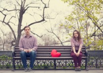 Sad teens sitting at the bench in park